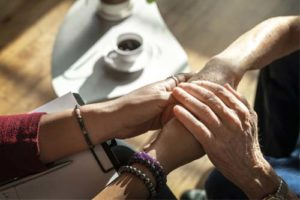 a group of people link hands at a drug and alcohol detox center